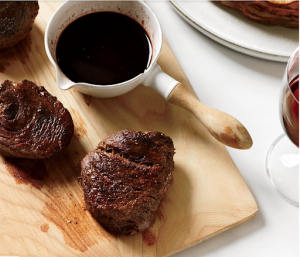 bison steaks on wood cutting board with bowl of fig balsamic sauce