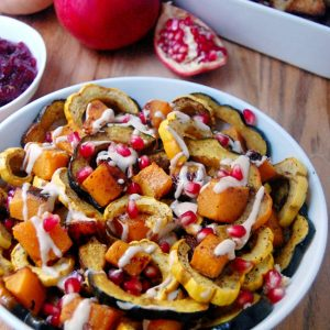 roasted squash and pomegranate seeds in white dish and whole pomegranate fruit on the side