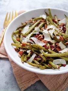 white bowl filled with green beans, shaved parmesan cheese and dried cranberries