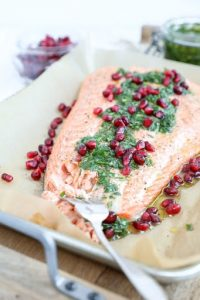 salmon filet topped with pomegranate seeds and herbs