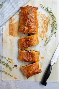 vegetable wellington on parchment paper next to chef knife and herb sprigs