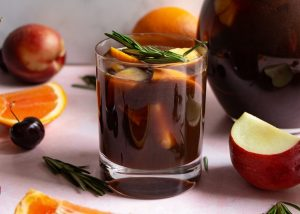 virgin prune sangria in glass mug surrounded by oranges, apples and rosemary sprigs