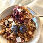 berry crumble in white bowl garnished with fresh blueberries
