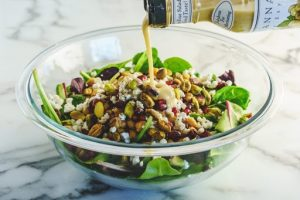 winter salad with pomegranate seeds and pistachios in glass salad bowl and dressing being poured over the top