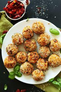 sun-dried tomato vegan meatballs on white platter with fresh basil leaves